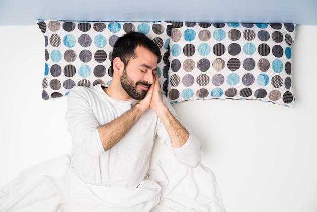 Homem na cama em vista superior, fazendo o gesto do sono em expressão dorable
