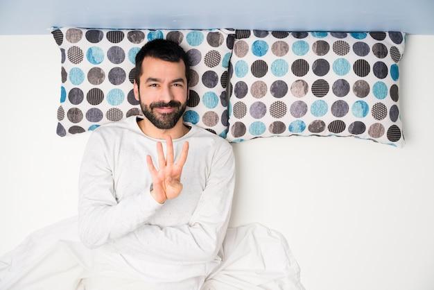 Homem na cama em vista superior feliz e contando quatro com os dedos