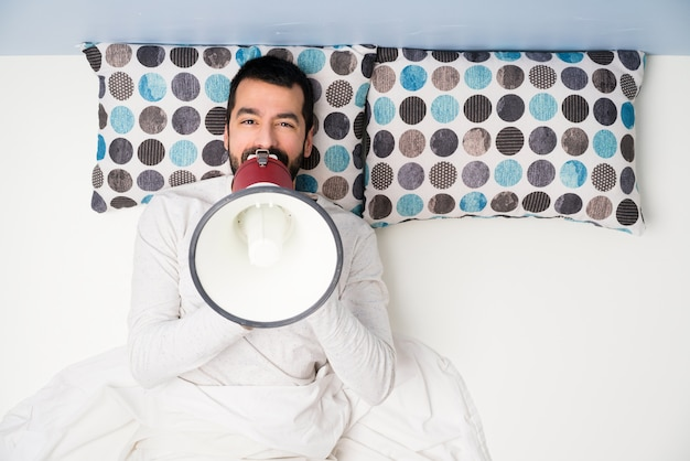 Homem na cama em vista superior, gritando através de um megafone