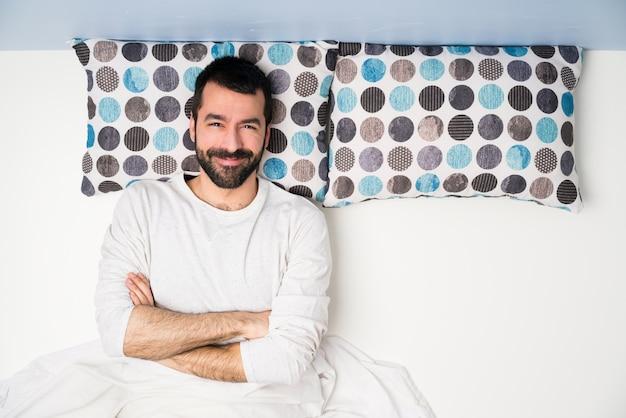Homem na cama em vista superior, mantendo os braços cruzados na posição frontal