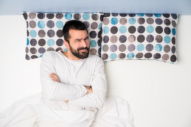 Homem na cama em vista superior, sentindo-se chateado