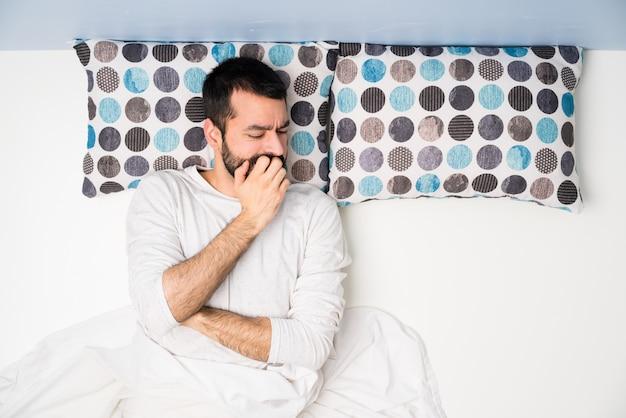 Homem na cama em vista superior, tendo dúvidas