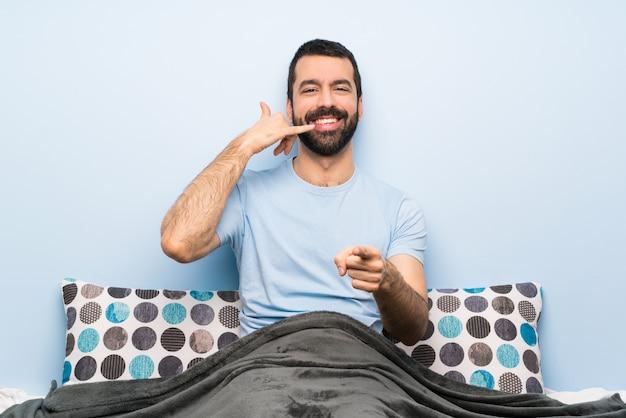 Homem na cama, fazendo gesto de telefone e apontando a frente