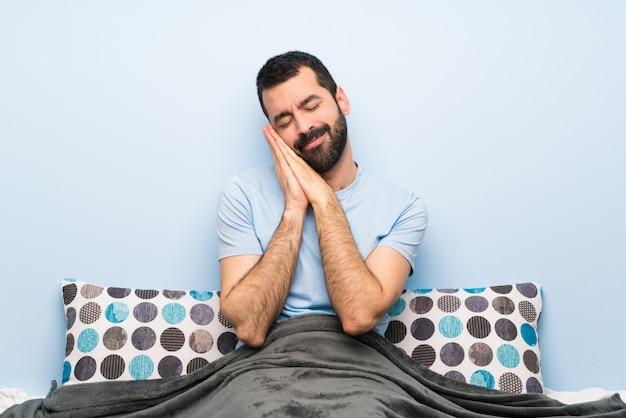 Homem na cama, fazendo o gesto do sono em expressão dorable