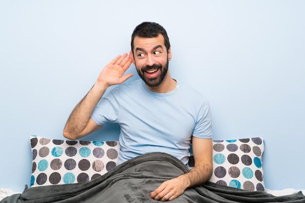Homem na cama ouvindo algo, colocando a mão na orelha