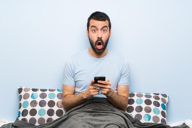 Homem na cama surpreso e enviando uma mensagem