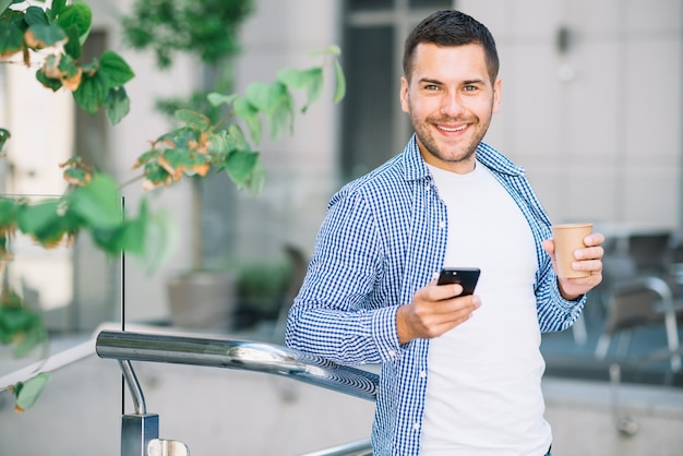 Homem na camisa usando o telefone perto do corrimão