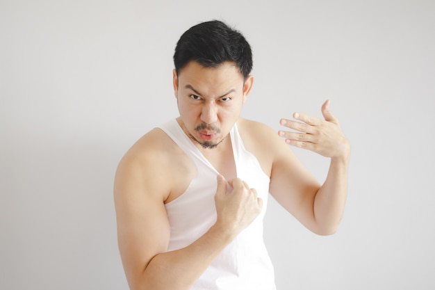 Homem na camisola de alças branca com expressão do tempo quente.