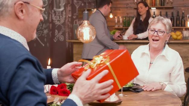 Homem na casa dos sessenta anos, dando à esposa uma caixa de presente vermelha. esposa surpreendente. homem e mulher felizes. casal idoso alegre.