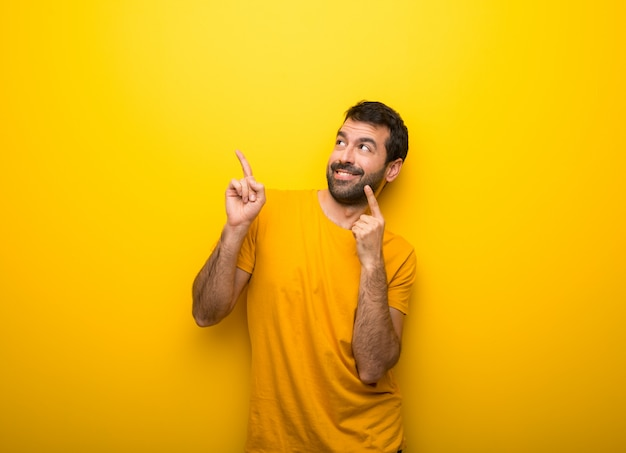 Homem na cor amarela vibrante isolada, apontando com o dedo indicador e olhando para cima