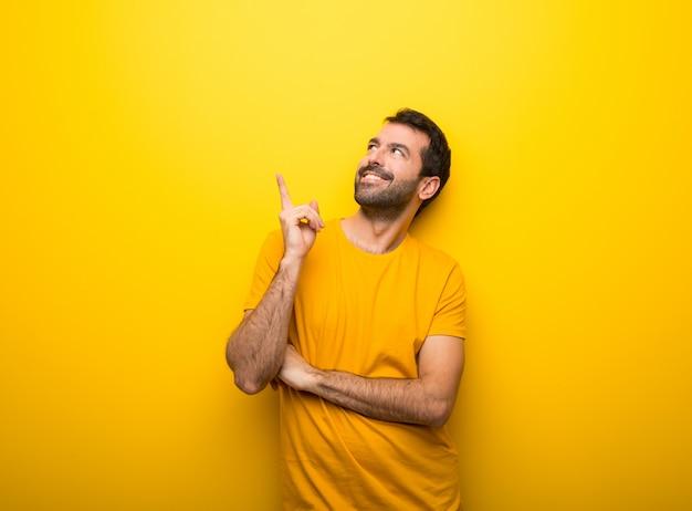 Homem na cor amarela vibrante isolada, apontando uma ótima idéia e olhando para cima