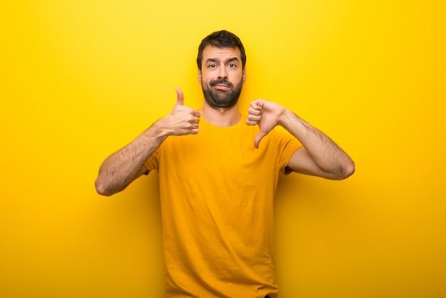 Homem na cor amarela vibrante isolada que faz o sinal bom-mau. indeciso entre sim ou não