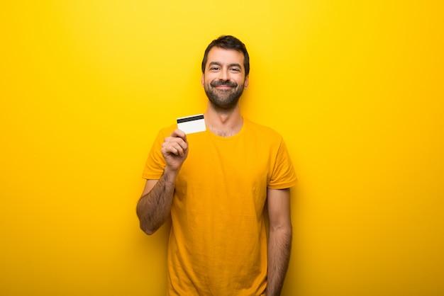 Homem na cor amarela vibrante isolada segurando um cartão de crédito