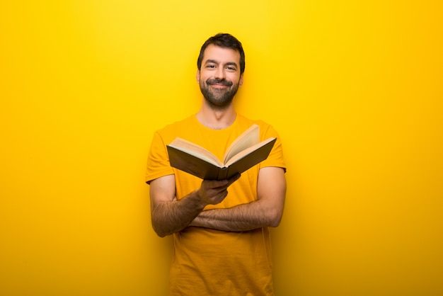 Homem na cor amarela vibrante isolada segurando um livro e dando-lhe a alguém