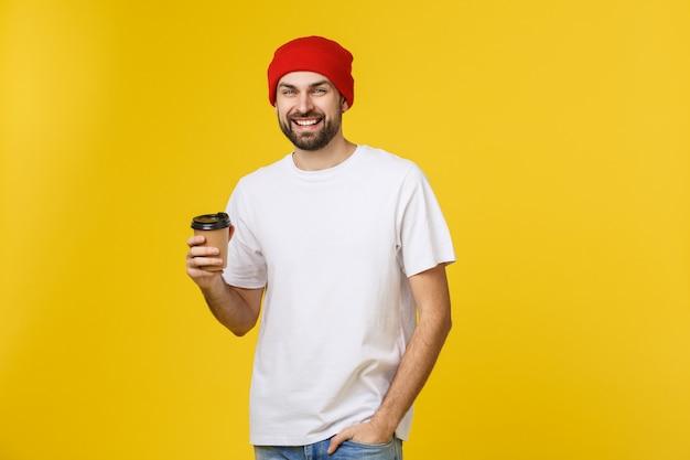Homem na cor amarela vibrante isolada, tomando um café no copo de papel para viagem e sorrindo, porque ele começará bem o dia.