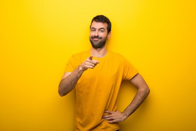 Homem na cor amarela vibrante isolado aponta o dedo para você com uma expressão confiante