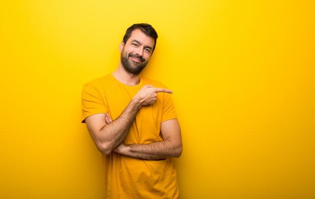 Homem na cor amarela vibrante isolado, apontando o dedo para o lado em posição lateral