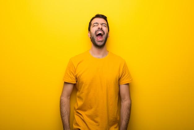 Homem na cor amarelo vibrante isolado gritando para a frente com a boca aberta