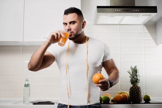 Homem na cozinha que prende um suco alaranjado e bebendo na cozinha. o conceito de um estilo de vida saudável