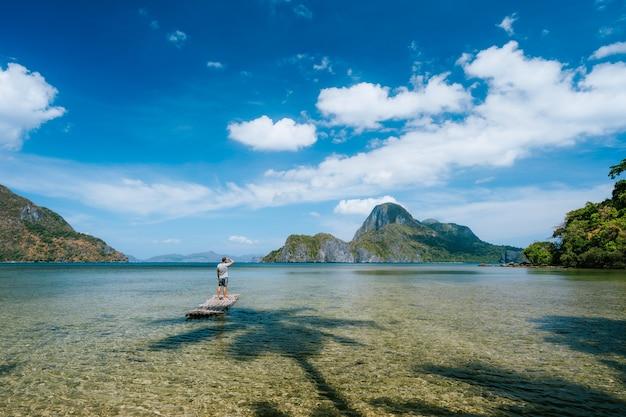 Homem na flutuação de bambu em lagoa rasa com vista panorâmica da lagoa rasa e ilhas na baía de cadlao.