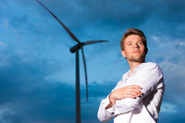 Homem na frente do moinho de vento e céu