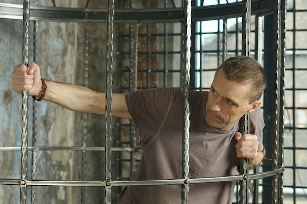 Homem na gaiola com as mãos em treliça de aço