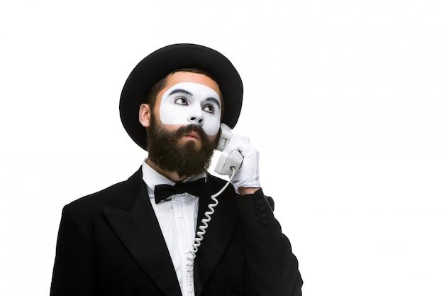 Homem na imagem mimica segurando um telefone.