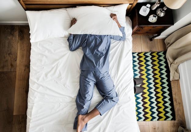 Homem na insônia de cama e conceito de poluição sonora