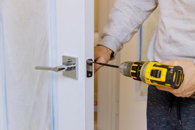 Homem na instalação de uma fechadura na fechadura da porta de madeira