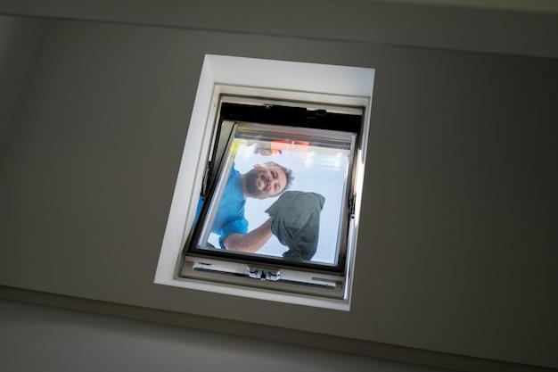 Homem na limpeza da janela do sotão