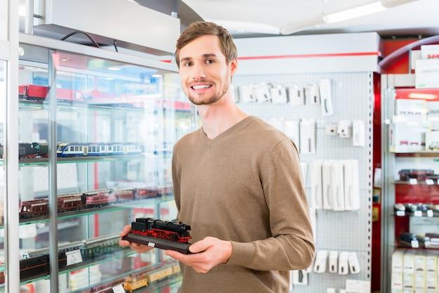 Homem na loja de brinquedos compra de ferrovia de modelo