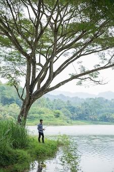 Homem na margem do rio, peixe de pesca
