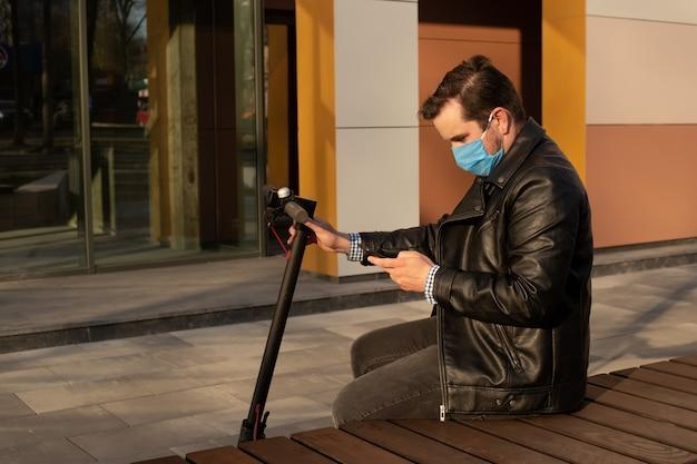 Homem na máscara médica na rua usando o smartphone, conceito de cuidados de saúde. quarentena do coronavírus.