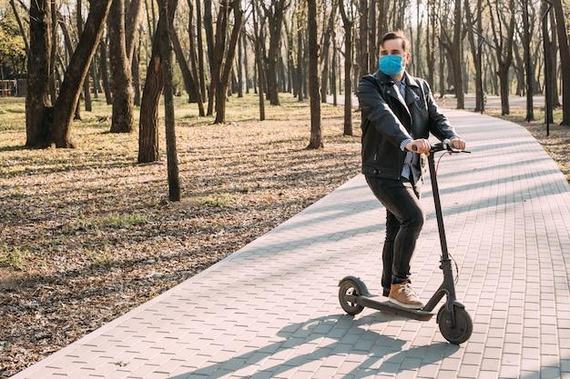 Homem na máscara médica protetora usando scooter elétrico, conceito de cuidados de saúde. quarentena do coronavírus.