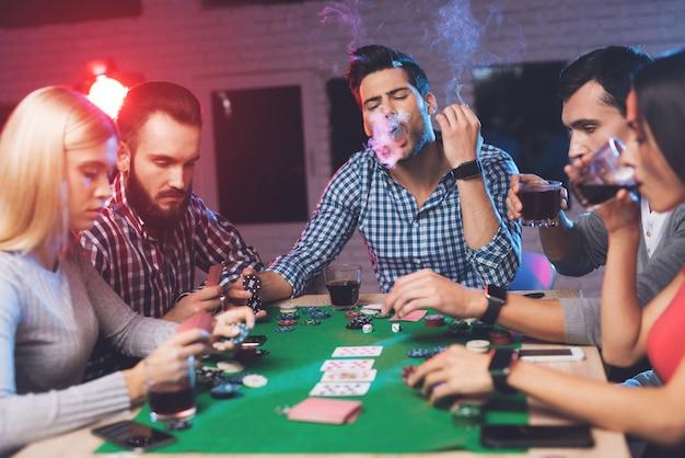 Homem na mesa de jogo fuma e fuma de sua boca.