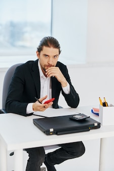 Homem na mesa documenta comunicação por tecnologia de telefone