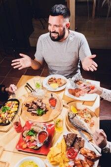 Homem na mesa grande com comida.