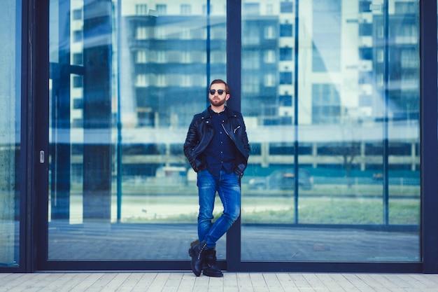 Homem na moda de jeans e jaqueta de couro