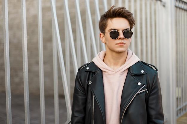 Homem na moda jovem hippie com um penteado elegante em óculos escuros em uma jaqueta de couro preta da moda em um moletom rosa fica perto de um portão de metal vintage. um cara americano atraente. moda