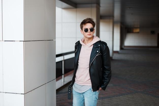 Homem na moda jovem hippie em óculos de sol pretos na elegante jaqueta preta no moletom rosa em jeans da moda em uma camiseta cinza está de pé dentro de casa. cara moderno com um penteado elegante.