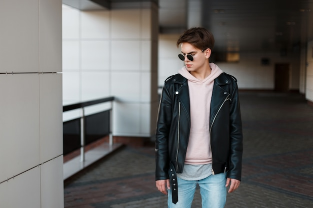 Homem na moda jovem hippie em óculos de sol pretos na elegante jaqueta preta no moletom rosa em jeans da moda em uma camiseta cinza está de pé na sala. cara sério e legal com um lindo penteado