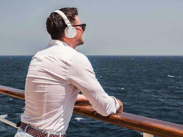 Homem na moda ouvir música em fones de ouvido brancos