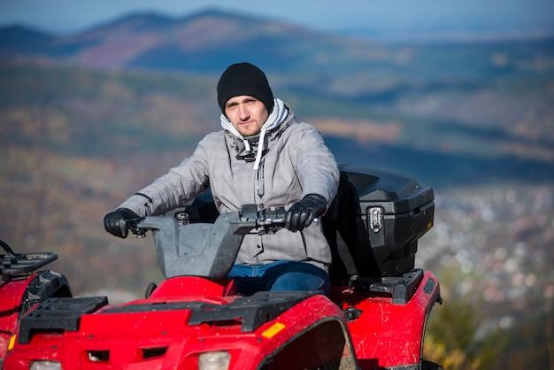Homem na moto quad vermelho