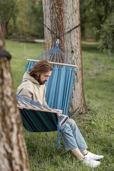 Homem na natureza, sentado na rede e trabalhando no laptop