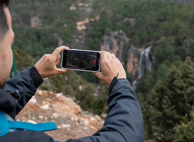 Homem na natureza tirando fotos com celular