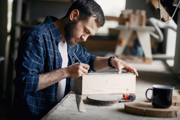 Homem na oficina com uma madeira