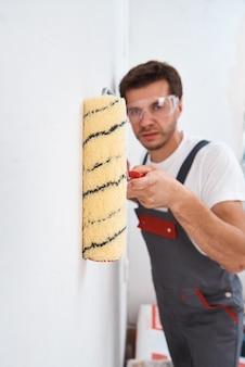 Homem na parede de pintura uniforme com rolo de pintura. conceito de renovação de casa