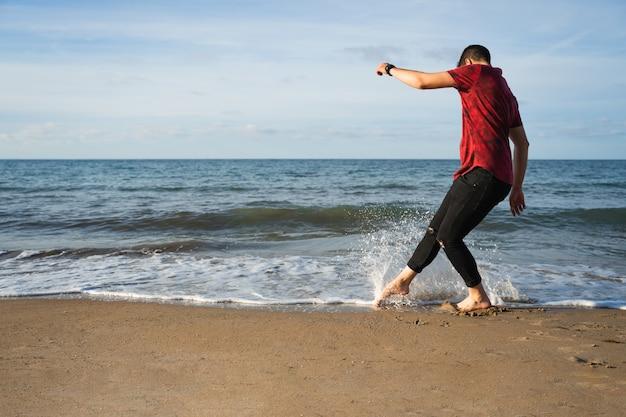 Homem na praia brincando com a água