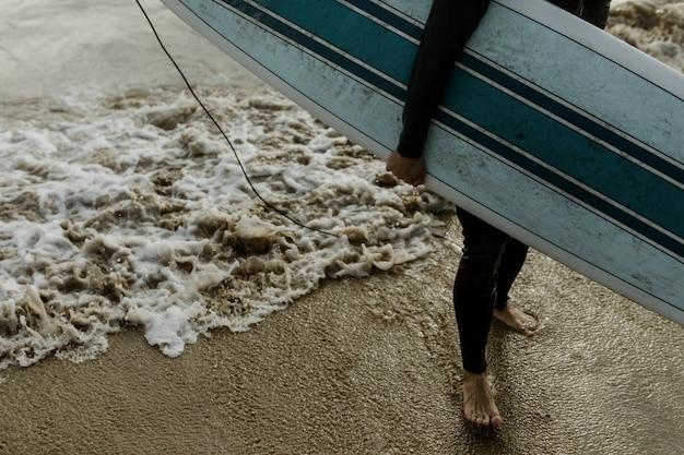 Homem na praia com sua prancha de surf