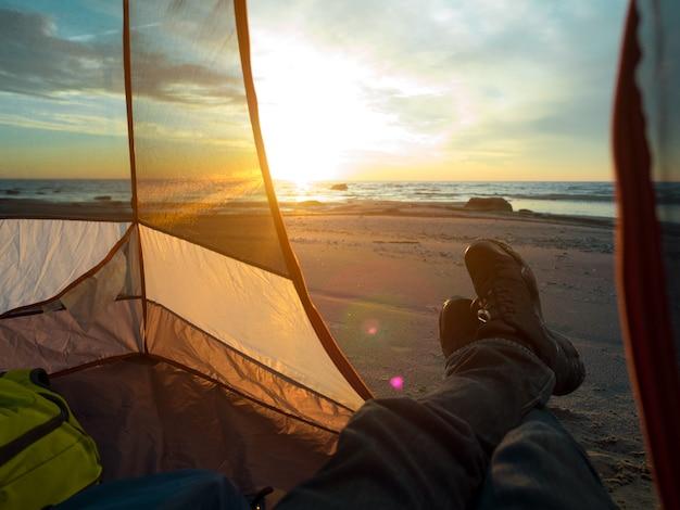 Homem na praia com um pôr do sol